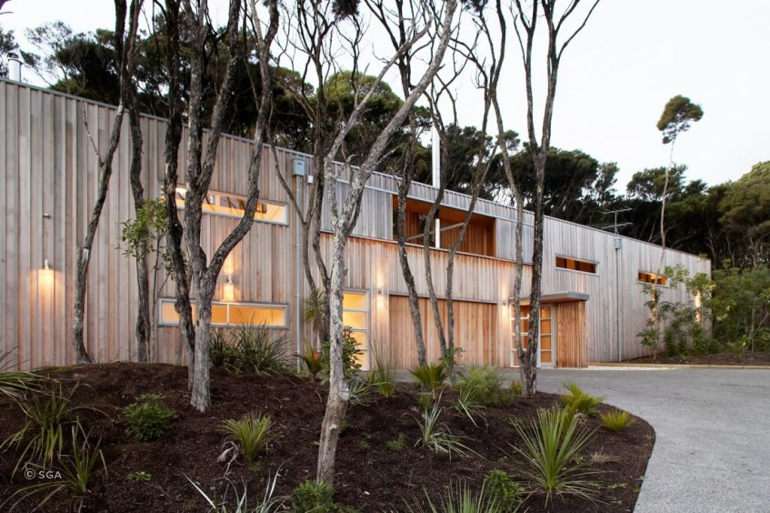 Point House is clad in vertical western red cedar, left to weather to respond to the surrounding Kanuka trees on the site.  By Strachan Group Architects. Photo by Patrick Reynolds.