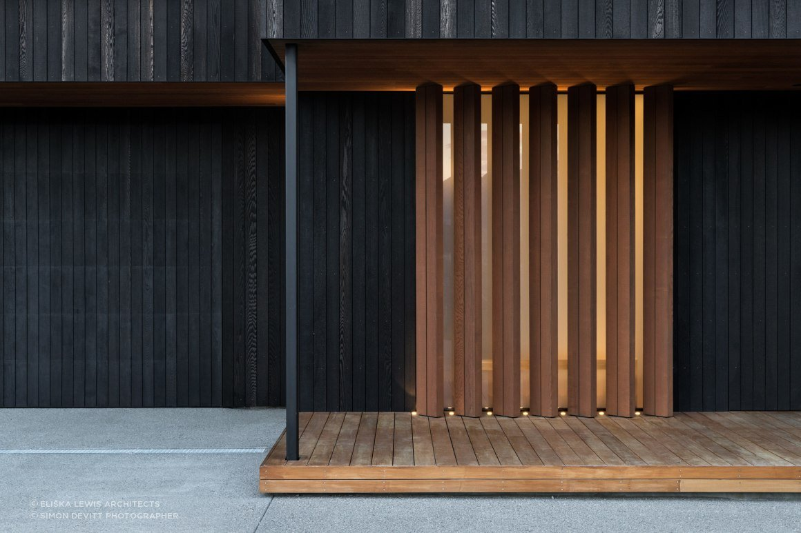 The main entrance features warm timber vertical louvres, where you enter into light-filled spaces that are arranged around an interior courtyard and a covered outdoor room.