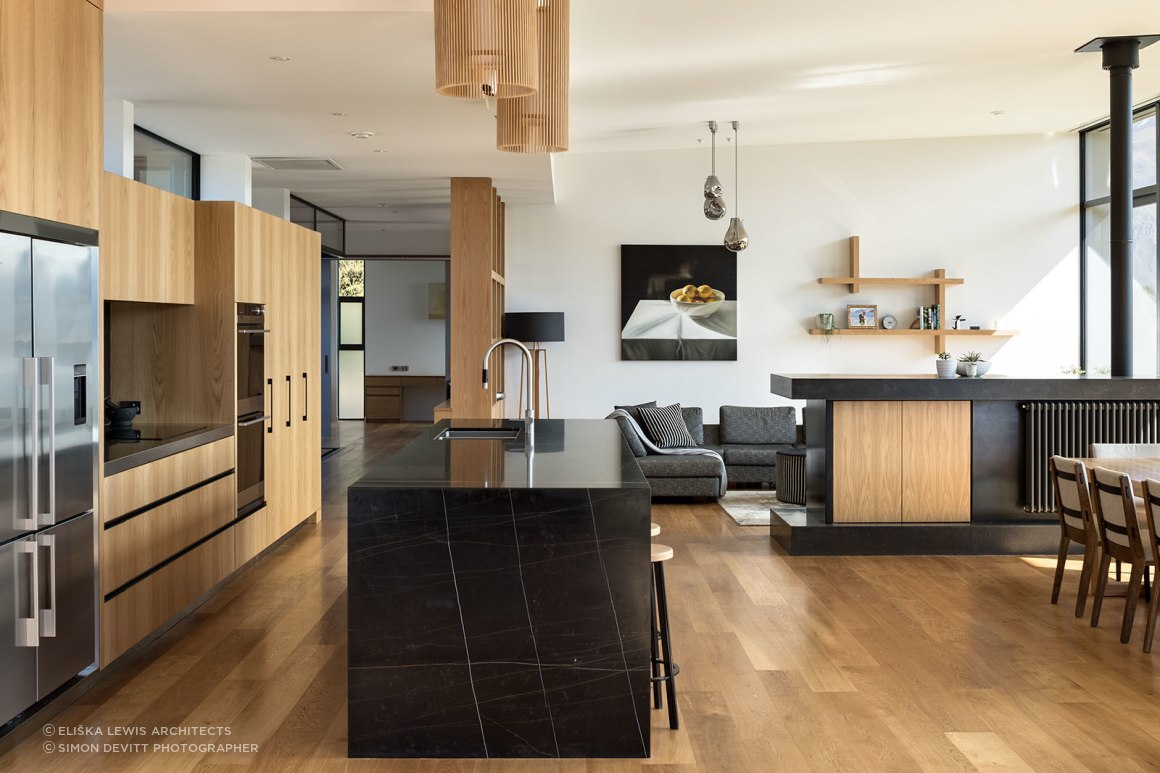 In the open-plan kitchen/dining/living space, a low custom-made room divide hosts a centrally-heated radiator, a television and storage.